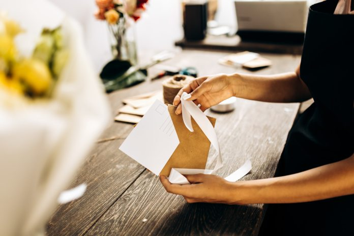 Florist is packing a postcard in an envelope with white ribbon on the wooden table