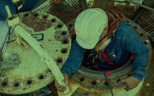 Worker climbing down into confined space