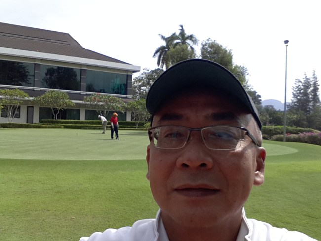 NIK'S SELFIE WITH THE PRACTICE GREEN IN FRONT OF CLUBHOUSE