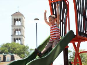 A boy with his hands in the air going down a slide