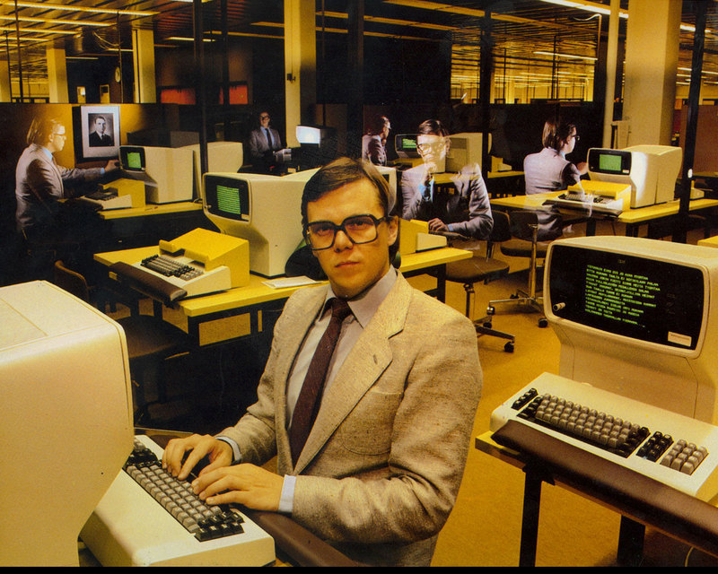 man with holographic images of himself at old computers