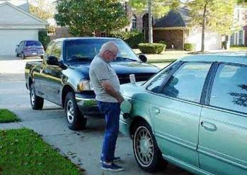 man peeing into gas tank