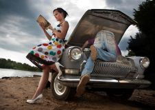 5057631 - pretty couple is trying to repair their old car using manual. rural background.