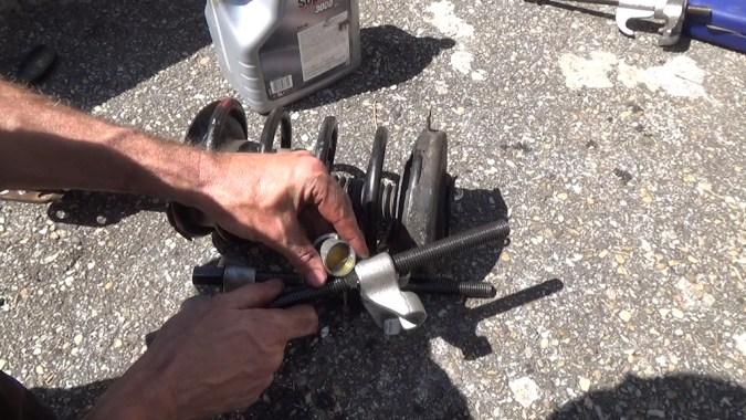 Lubrifiez les tiges filetées du compresseur de ressort