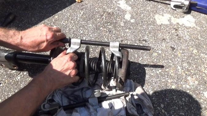 Positionnez le compresseur de ressort parallèlement à l'axe de l'amortisseur