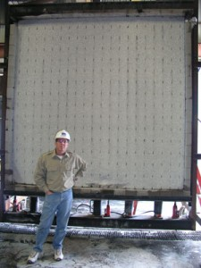 BuildBlock CEO Mike Garrett stands in the front of the post-test wall which is loaded down with 12,000 lbs per lineal foot of pressure.