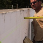 Checking the wall for plumb after the pour