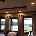 Master bedroom with large windows and raised ceiling