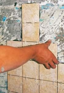 man tiling a wall