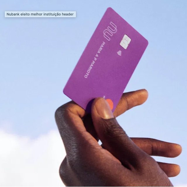 A hand holding a purple Nubank credit card to the blu sky. Nubank is elected by Forbes as the best financial institution in Brazil for the third consecutive year