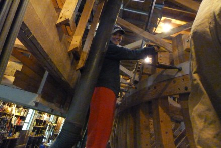 Gina helps steam-bend the first cuddy deck plank around the curve of the bow.