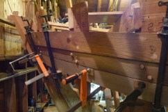 Aft plank bent in, cooling. Some bungs trimmed, some not.
