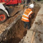 Hand digging trench for utility services around existing pipework and cables