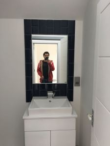Bathroom sink Metro tiles framing mirror