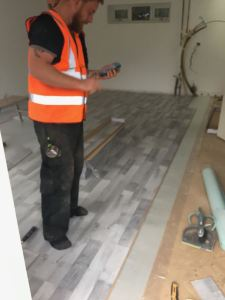 Grey oak laminate wooden flooring being installed