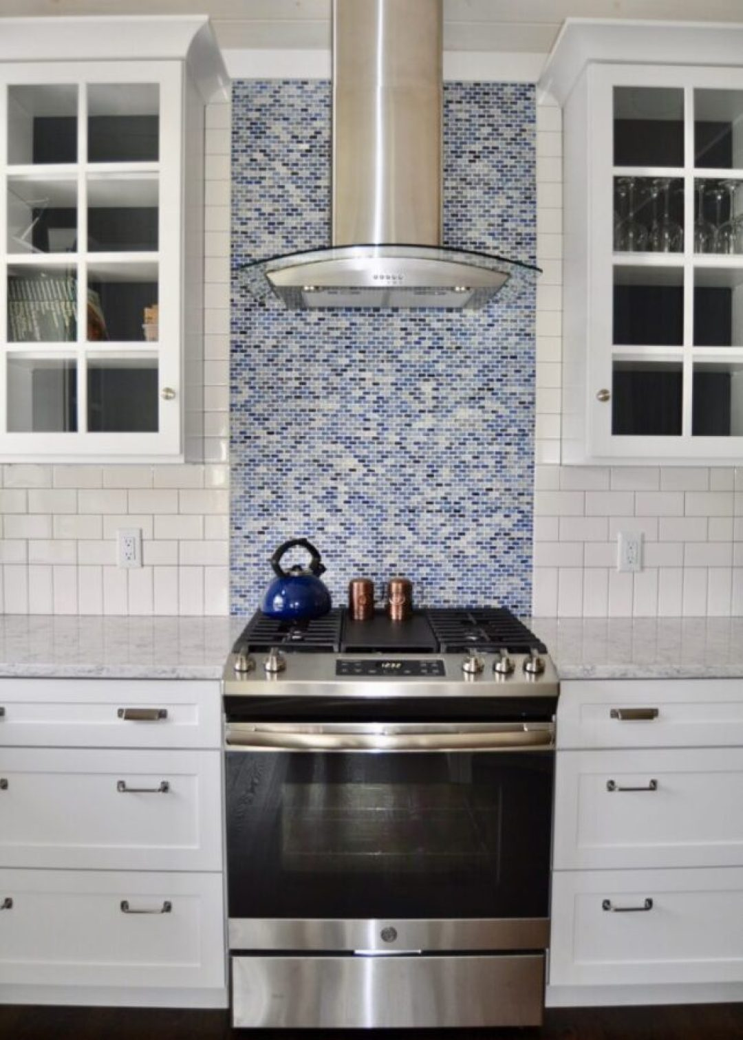 Subway tile & blue backsplash behind the range