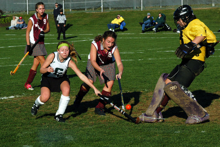 Carlisle's Melissa Moist and Mechanicsburg's Katie Hamilton fight for the ball but Mechanicsburg's goalie, Karen Thompson kicks it out during the first round of District 3 field hockey playoffs at Camp Hill.