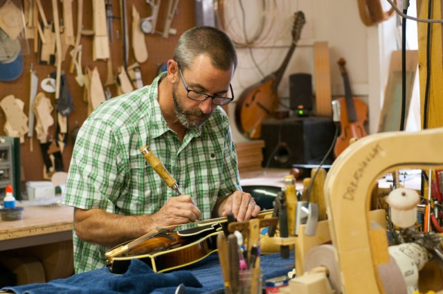 Austin Clark putting the final touches on a mandolin