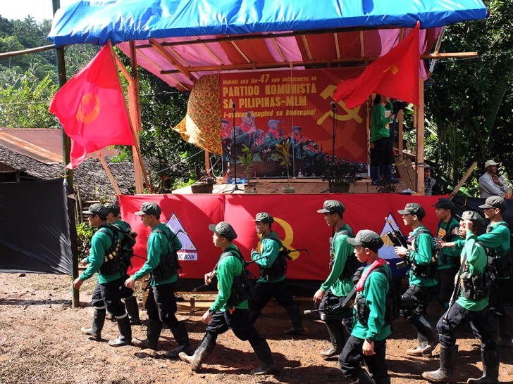 New People's Army fighters walk before their movement's standards as they take their positions for the start of the Communist Party's anniversary celebrations. (Kitcharao, Agusan del Norte)