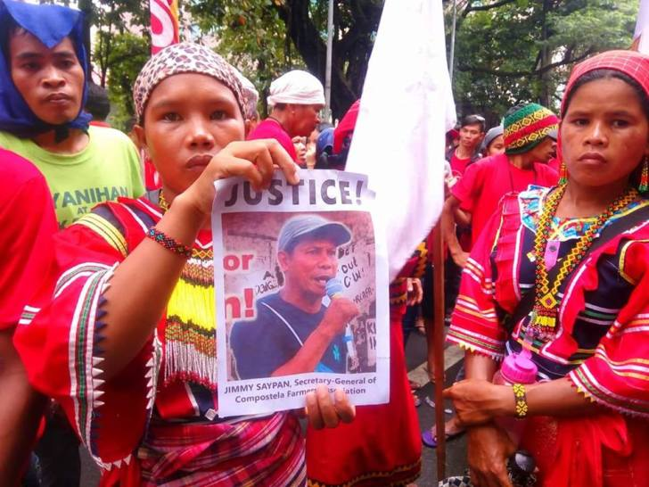 Manobo leader Cristina Lantao holds a picture of Jimmy Saypan, secretary general of Compostela Farmers' Association who was killed by suspected soldiers last week (Photo by Kilab Multimedia)