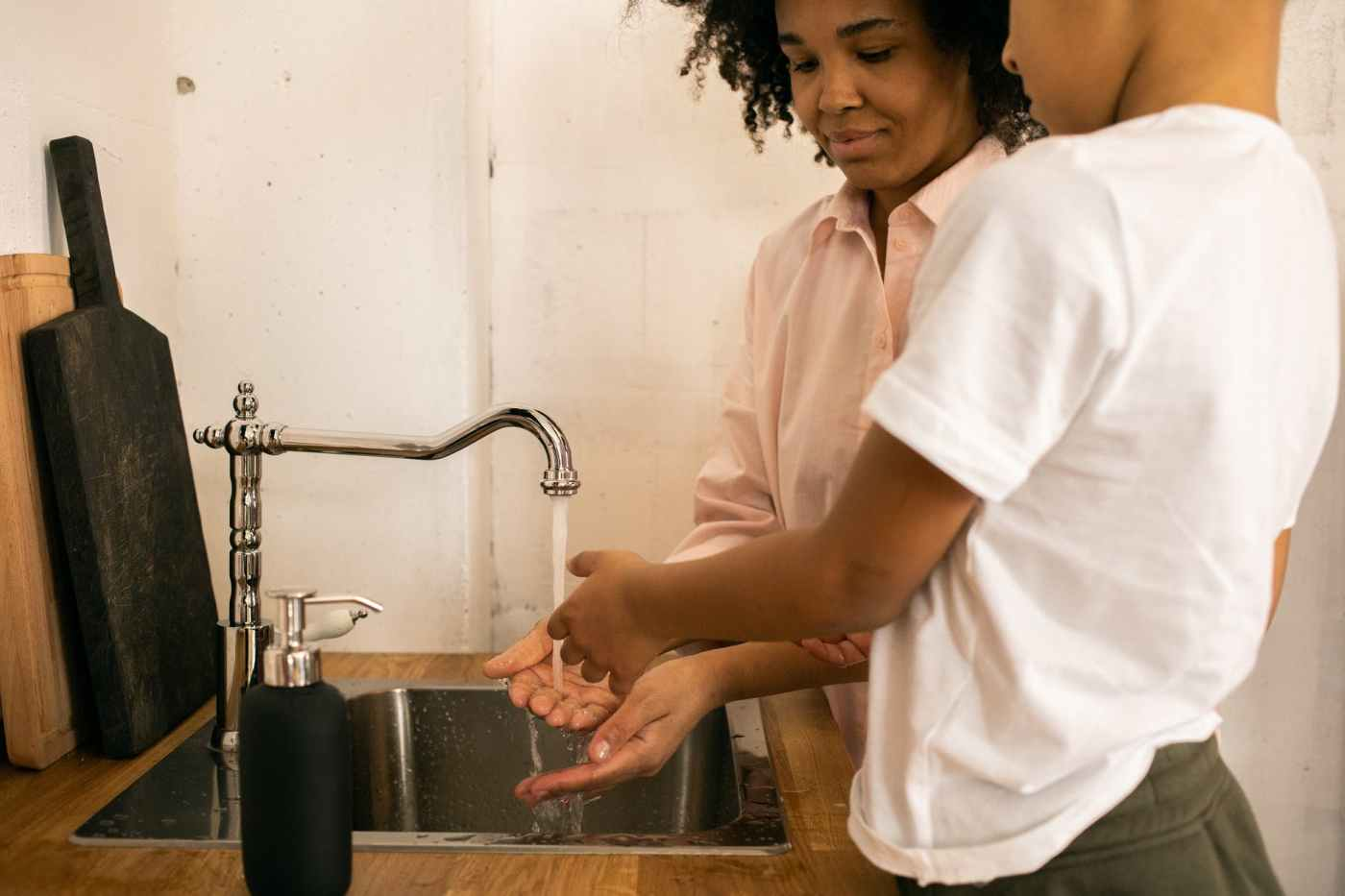 black woman with anonymous son washing hands