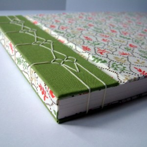 A custom sketchbook in a coral-patterned white fabric. A vertical green stripe runs down its left hand side, acting as a background for the decorative stitching that binds the book.