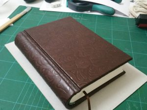 A chunky burgundy-brown leather book with embossed covers