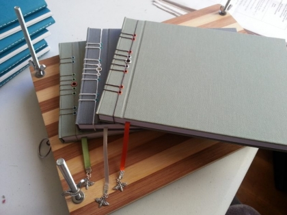 A stack of three stab bound books in different colours of plain bookcloth