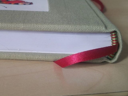 A handbound book in pale green cloth with red details