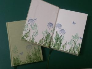 Two sage green medium journals with blue & green handprinted plants on the covers and endpages