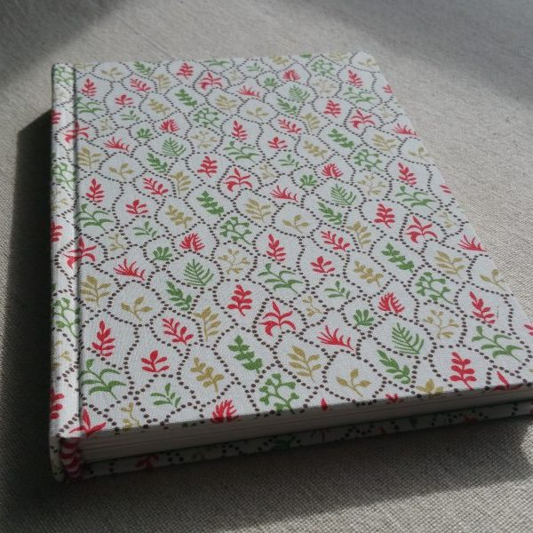 A white A5 sketchbook with a green and red pattern