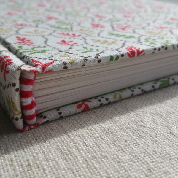 The corner of a medium sketchbook in white, red, and green