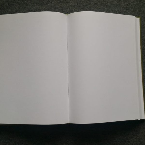 A large journal lies open on its back to reveal blank white pages inside.