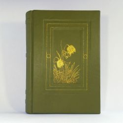 A large green leather journal with a golden image of snake's head fritillaries on the cover.