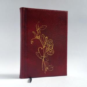 A medium leather journal in red leather, with a golden illustration of sweet peas on the cover.