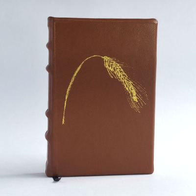 A small leather journal in tan brown with a gold illustration of rye on the cover