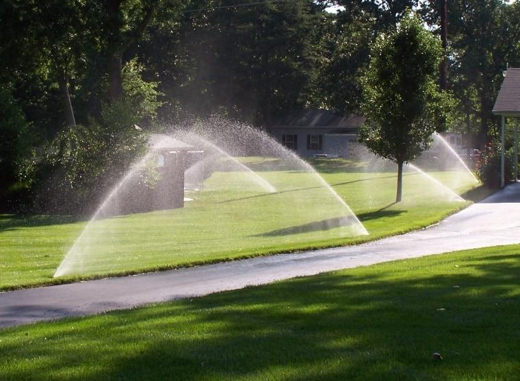 image of sprinklers watering a yard