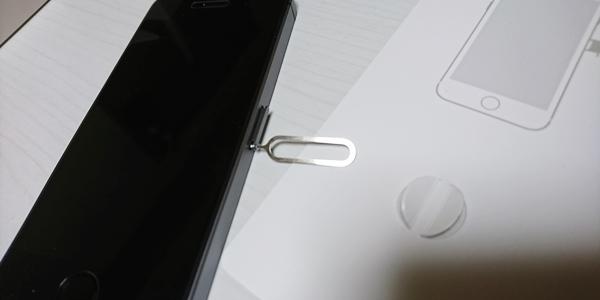 SIMピンをiPhoneのSIMトレーに押し込む