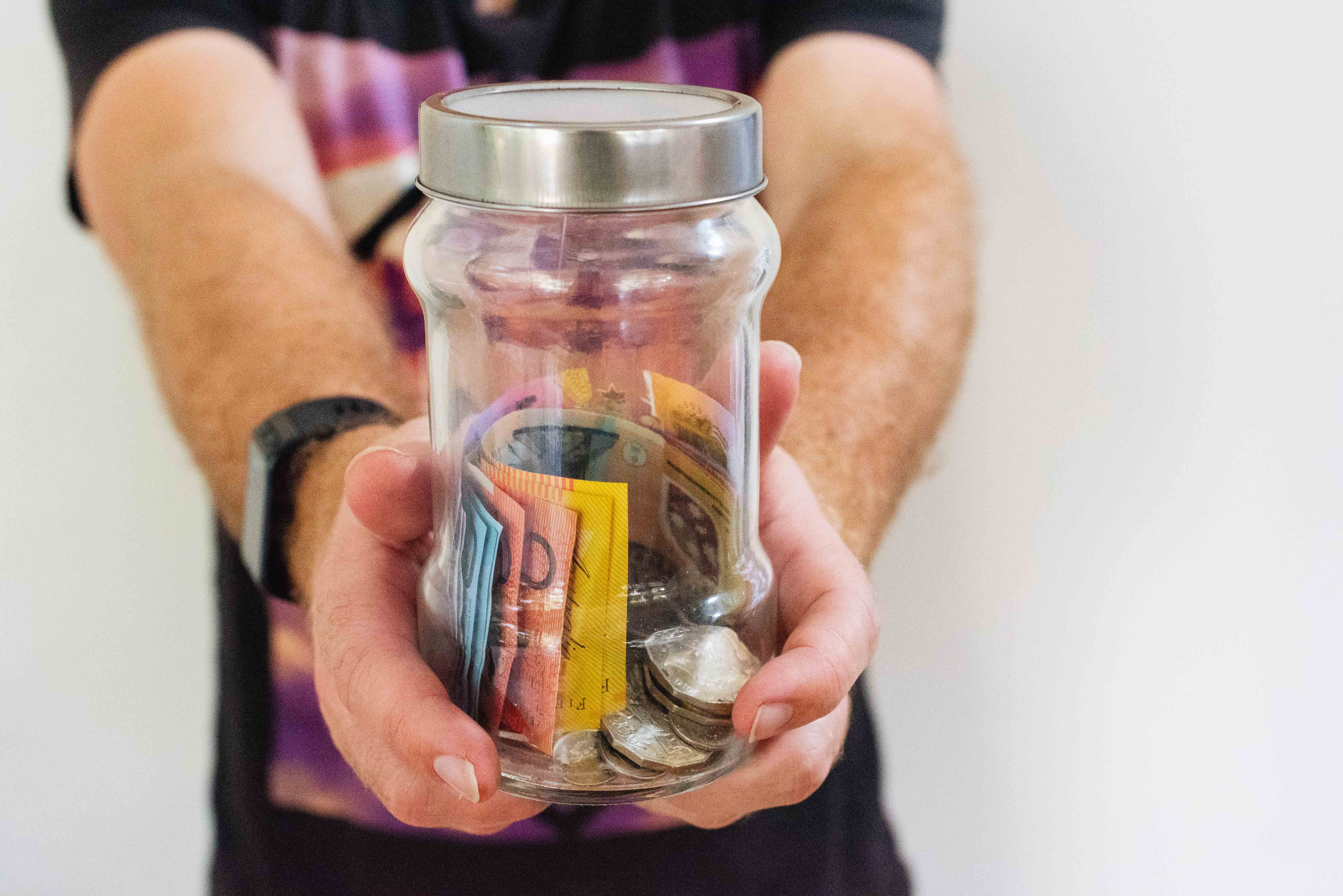 Person holding jar with money