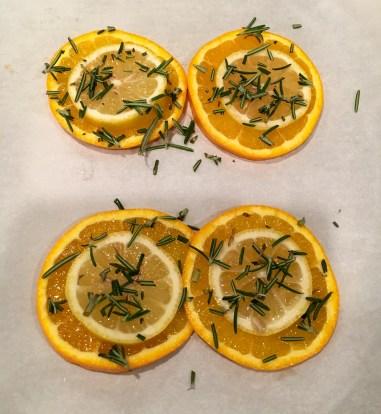 Layering the lemon and orange slices and adding rosemary