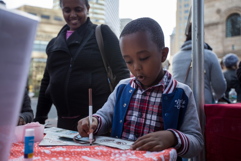 Robby Getachew, 5, watched by Zemen Takele, draws at the Woodland Way booth at the Boston Book Festival street fair in Copley Square, Boston, Mass., on Saturday afternoon. Dozens of vendors, schools, libraries and food trucks participated in the fair. Photo by Alexandra Wimley