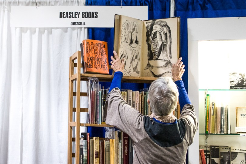 "BOSTON, October 29, 2016 - Beth Garon, 69, from Beasley Books of Chicago, Illinois, adjusts a book on display at the fair. ""I and my husband have been coming to this book fair since the early 1980s. It's a fun thing to do,"" said Garon. Photo by Kankanit Wiriyasajja/BU News Service"