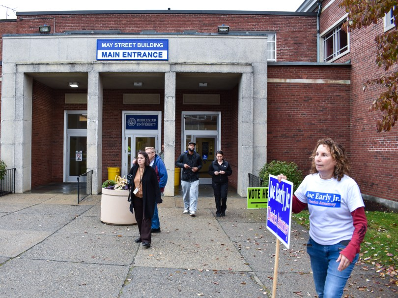 Photo Caption: Laura Foster (right) stands outside the May Street Building at Worcester State as early voters walk in and out. She and several other people stood outside holding signs for various candidates, Nov. 2, 2018. Photo by Zachary Eilert