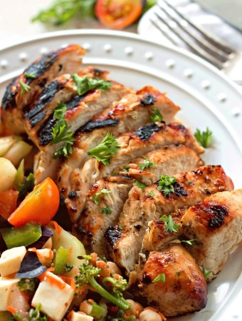 Mustard Chicken Marinade sitting on a white plate with roasted vegetables