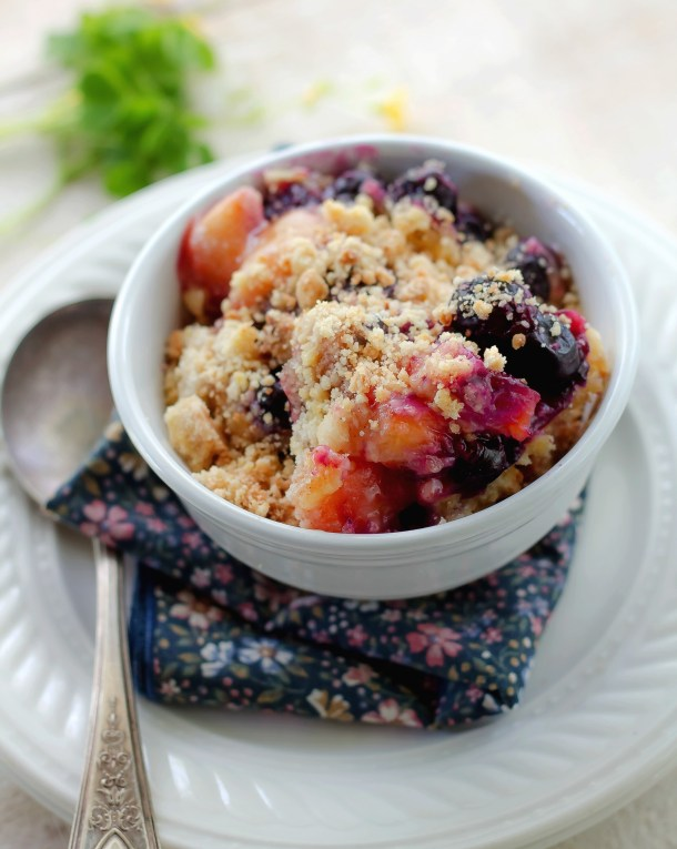 Old Fashioned Peach Blueberry Dessert in a white bowl sitting on a blue napkin on a white plate with a spoon