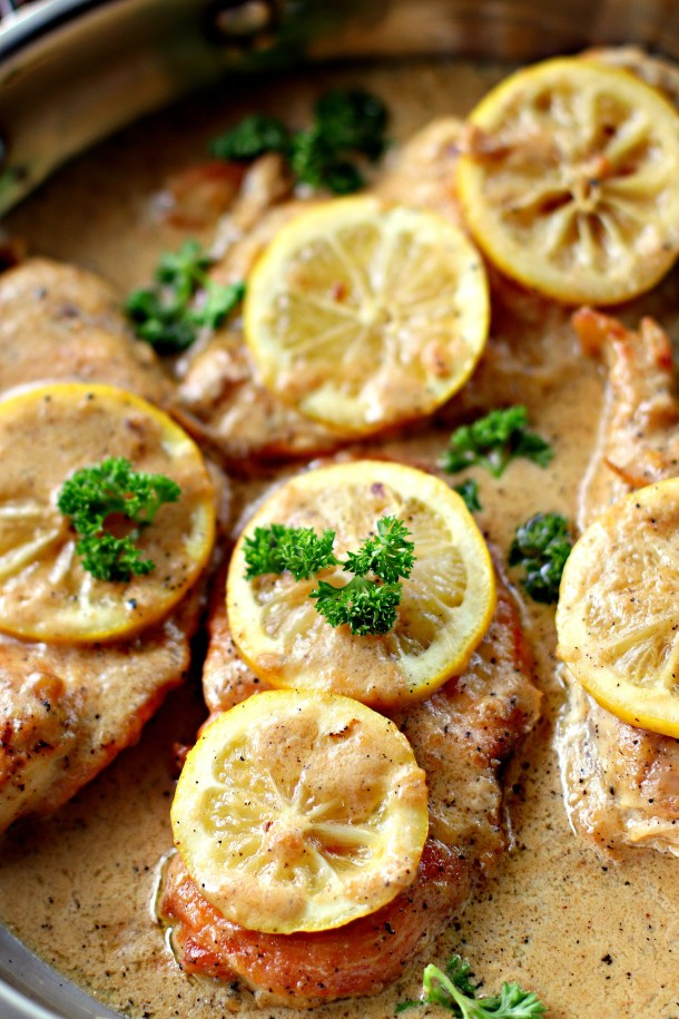 Creamy Lemon Chicken Thighs in a metal saucepan garnished with lemon slices and parsley