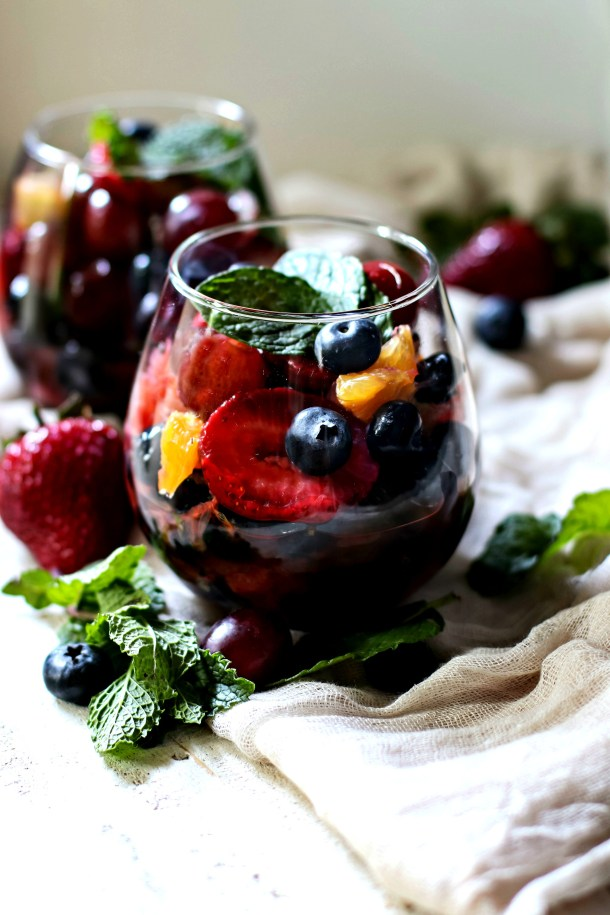 Lime Honey Mint Fresh Fruit Salad Sauce over fresh fruit in a dessert dish garnished with fresh mint