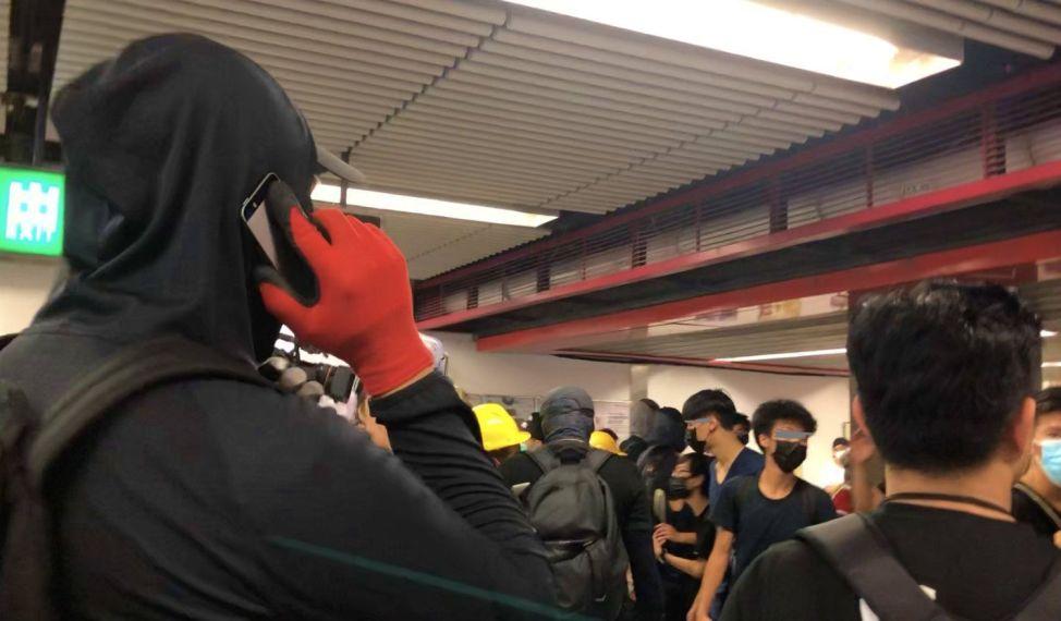 9月8日、勇武派が一時的に占拠したセントラル駅構内で、仲間と連絡を取り合っているらしき覆面部隊の男性(左)。他の比較的軽装のデモ参加者と混じっているが、トラブルは起きていない。