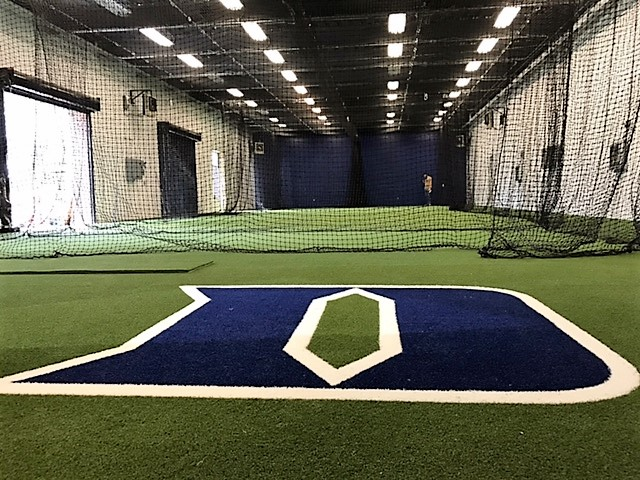 ... Softball With A New Nylon Backstop System And A Custom Indoor Hitting  Facility. The Indoor Facility Has Custom Logo Turf And Retractable Netting.