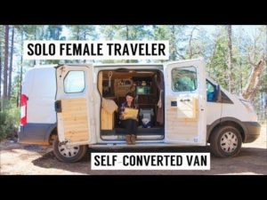 "An image of a woman sitting at a computer in her van home, with the title ""Solo Female Traveller, Self-Converted Van"""